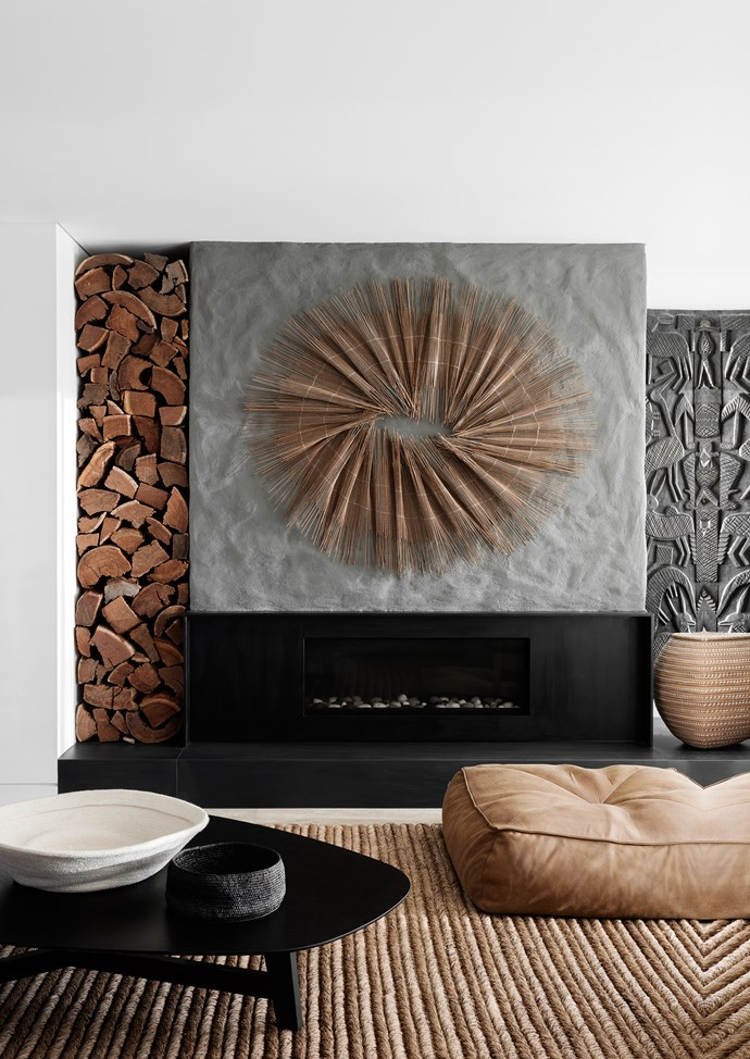 The fireplace surround is in honed black basalt. A Jardan 'Alby' leather ottoman sit on a 'Manzanilla Malay' abaca rug from International Floorcoverings. Wall installation by Tracey Deep.