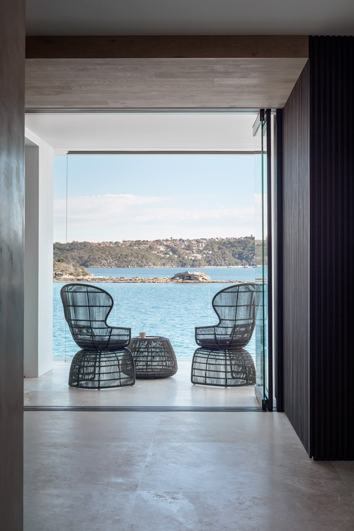 B&B Italia 'Crinoline' armchairs and 'Canasta 13' side table provide the perfect waterside relaxation spot. 'Lara Cream' stone flooring from Di Lorenzo.