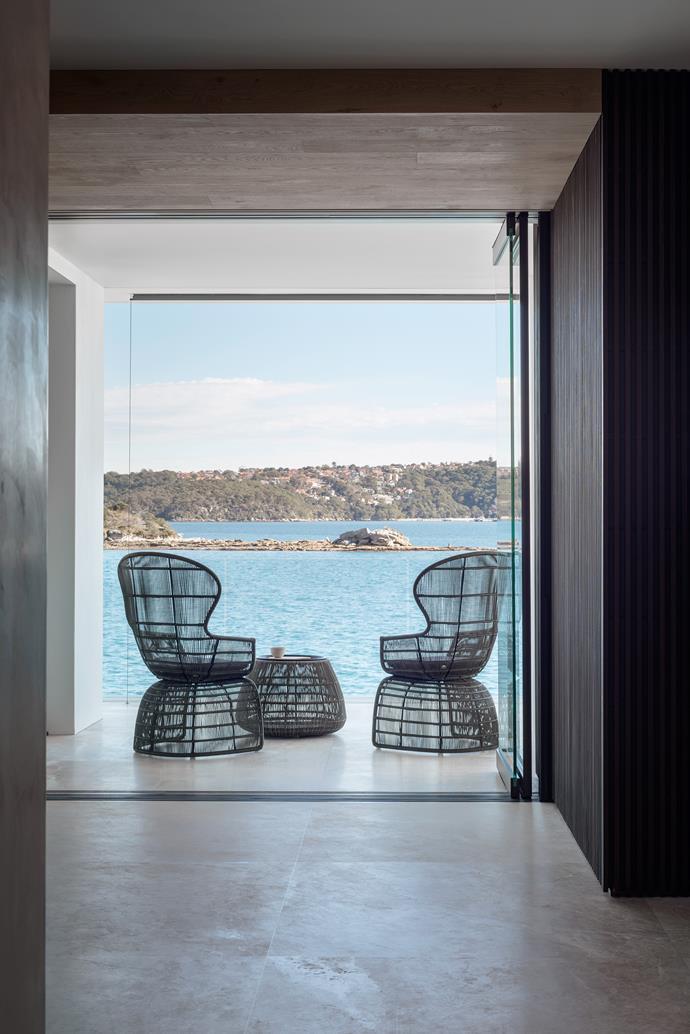 B&B Italia 'Crinoline' armchairs and 'Canasta 13' side table provide the perfect waterside relaxation spot. 'Lara Cream' stone flooring from Di Lorenzo.
