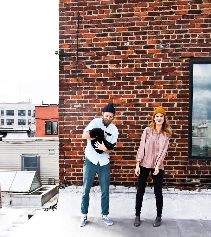Simon and Jess, with cat Lexington, can climb through their bedroom window to reach the roof terrace with its views over Williamsburg's rooftops.