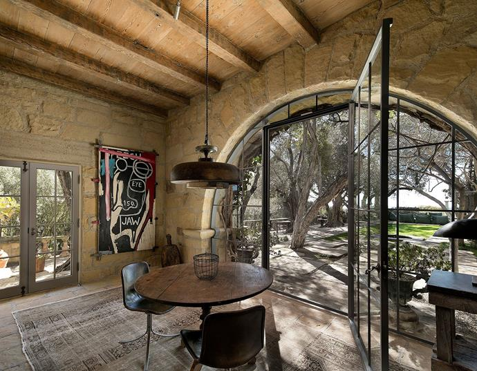 Just off the kitchen, this informal dining room looks out over the manicured gardens through a sandstone archway.