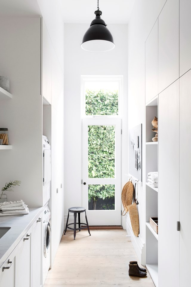 "Having a clean and [organised laundry](https://www.homestolove.com.au/how-to-organise-your-laundry-10157|target=""_blank"") is #lifegoals. Ample storage is the secret to keeping your laundry looking shcmick, even when there's baskets of dirty clothes and cleaning products lurking behind closed doors. *Photo:* Steve Ryan"