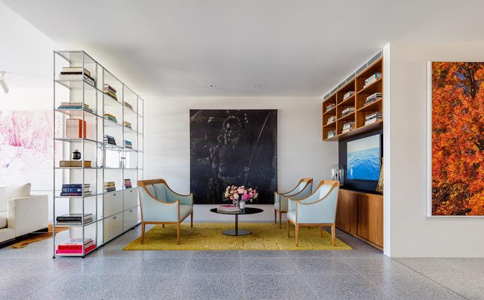 The television room has seating, inherited from Nick's grandmother, arranged around a Minotti coffee table from De De Ce on a rug from Tibet Sydney. USM shelves from ECC Lighting + Furniture. Artworks by Fiona Lowry (left), Daniel Boyd (centre) and Ryan McGinley (right).