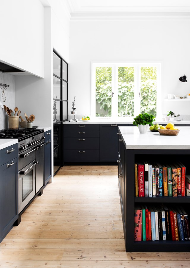 "This elegant black kitchen in an [updated heritage home](https://www.homestolove.com.au/elegant-heritage-home-in-melbourne-by-ali-ross-design-5014|target=""_blank"") features plenty of storage, with a book shelf beneath the kitchen island, steel framed display cabinets and a walk-in pantry. *Photo: Martina Gemmola*"