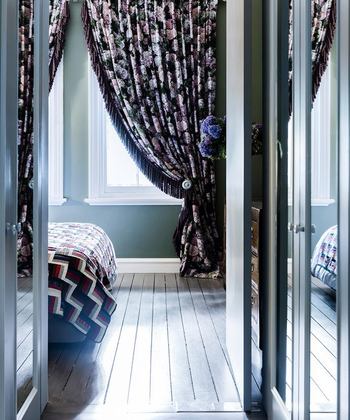 Floor-skimming drapes with a bold floral print add drama to this bedroom. *Photo: Maree Homer*