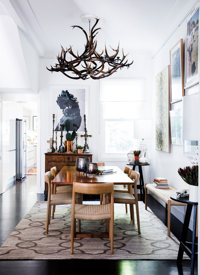 A deer-antler chandelier presides over a rich assemblage of art and collectables. Table, from Planet Furniture. Chairs and bench, from Great Dane. Black cockatoo photographic artwork by Leila Jeffreys.