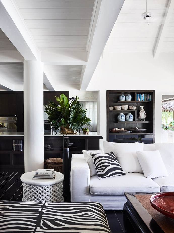 Contrast defines the kitchen/living area. Hand-picked objects stand proud in dark cabinetry and bold prints lift the white sofas.