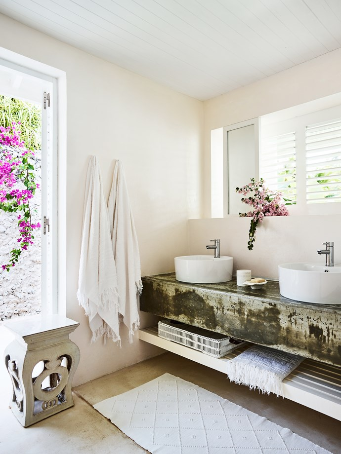 A bathroom in the two-bedroom guesthouse has smooth concrete surfaces and a vine-draped privacy wall in coral stone.