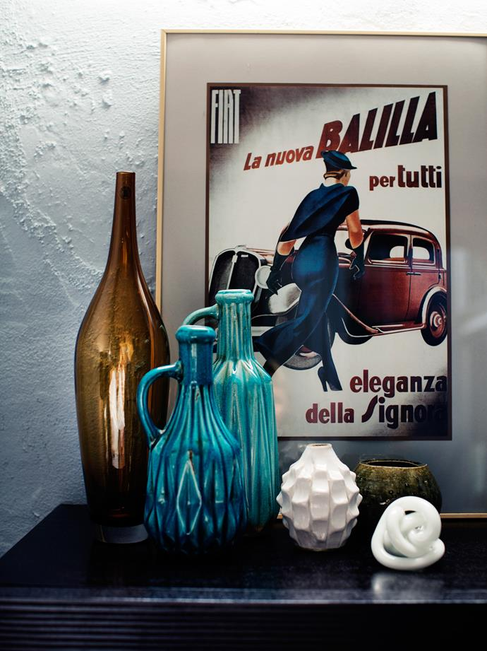 A vintage Italian car advertisement presides over this pretty, tonal vignette atop a chest of drawers.