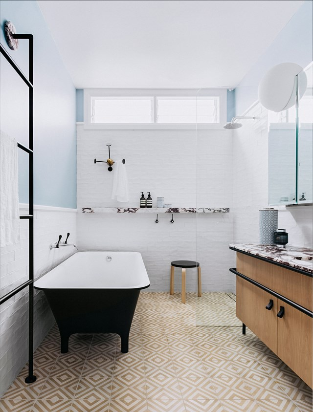 It might look as if there's a lot going on with the various materials used in this bathroom, but because all the hues and materials fall within a natural palette, the overall effect is harmonious. Popham 'Diamond In The Rough' floor tiles, add warmth add texture as well as a nice contrast against the soft blue and strong black accents.