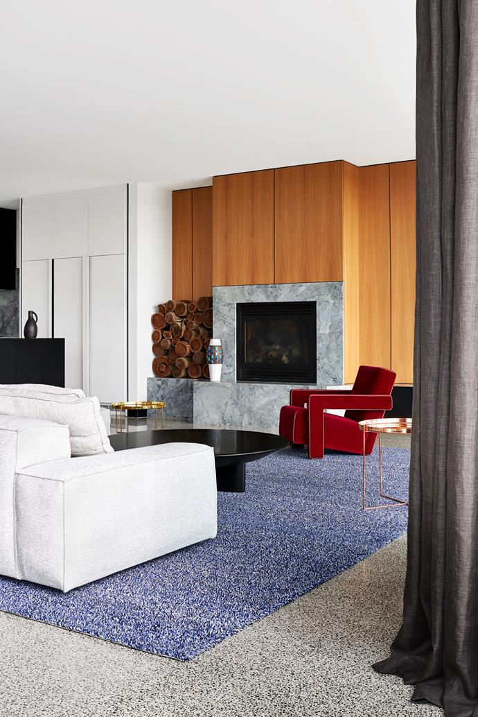 A Cassina 'Utrecht' chair in red pops against the custom rug in Blueberry from Bibi Viro. Living Divani 'Neo Wall' sofa from Space. Cassina 'Accordo' coffee table from Cult. E15 'Habibi' tray tables (left and right). A Bitossi vase from Hub sits near the fireplace.