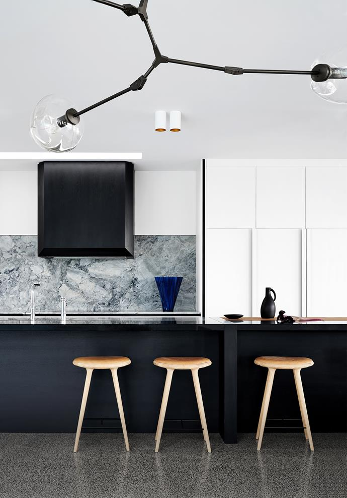 The kitchen has a splashback in 'White'Fantasy' stone from Artedomus. Lindsey Adelman chandelier. Mater stools from Cult. 'Shanghai' vessel from Space. On benchtop, Ay Illuminate ceramic jug and plate from Safari Living.