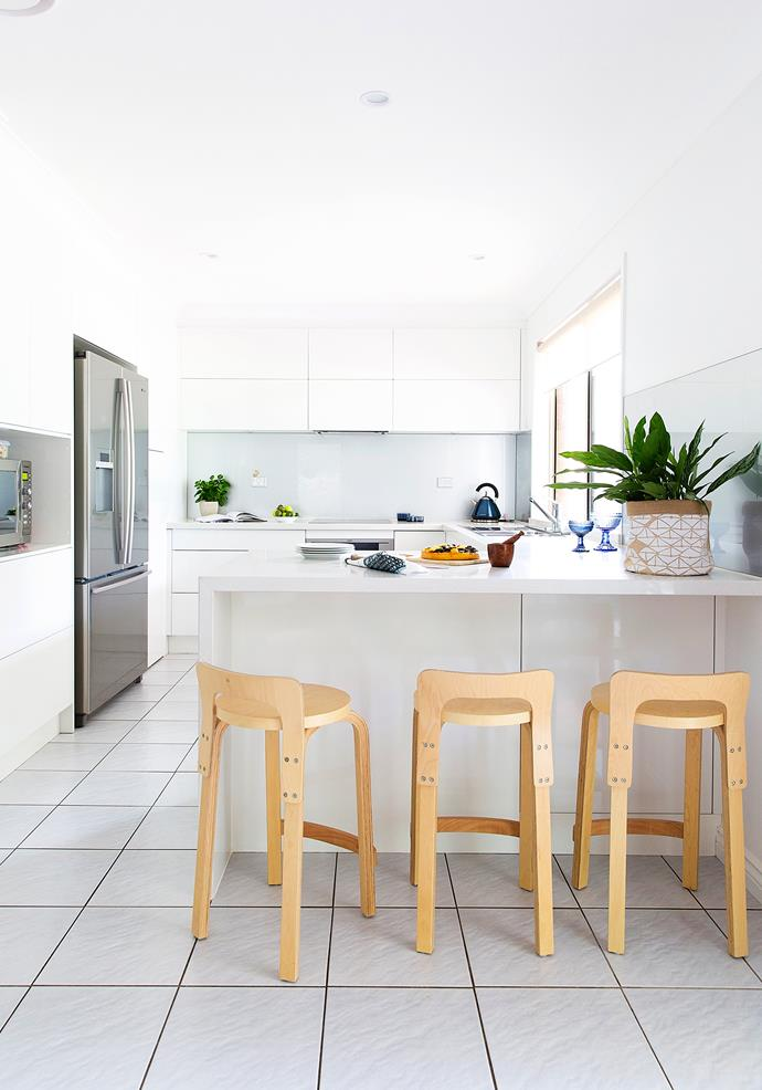 The crisp kitchen is warmed with replica Alvar Aalto bar stools in Oak, from Matt Blatt.
