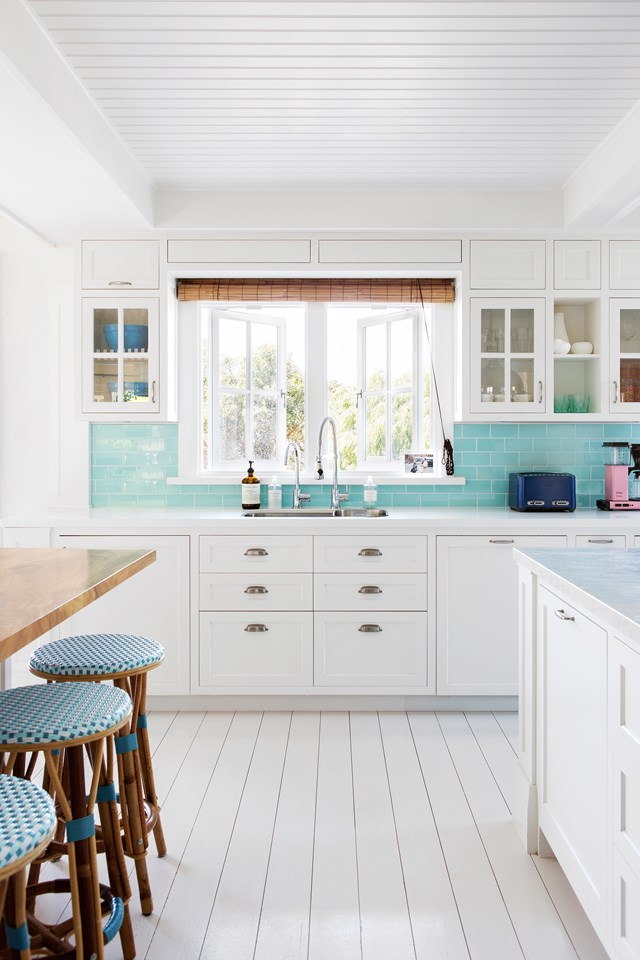 "A gentle ocean blue pops against the white of the joinery in the kitchen of this [Hamptons inspired holiday home](https://www.homestolove.com.au/a-hamptons-inspired-holiday-home-south-of-perth-5122|target=""_blank""). Photo: Angelita Bonetti / *Australian House & Garden*"