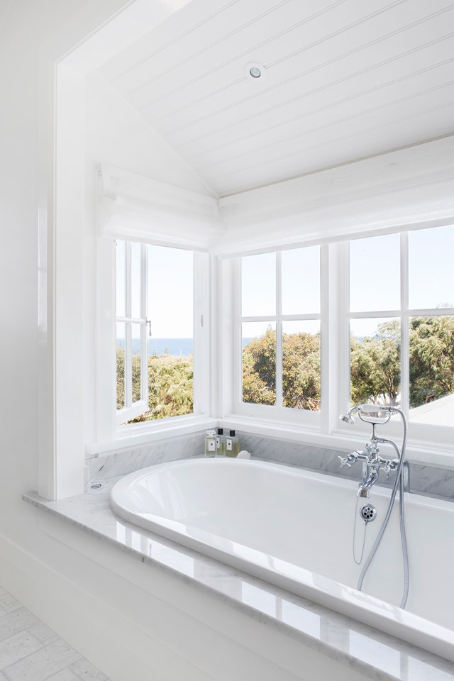 "Sinking into a tub full of bubbles and enjoying views of treetops and the ocean beyond sounds like an evening well-spent. This luxurious ensuite features an [inset bathtub](https://www.homestolove.com.au/inset-bathtubs-19355|target=""_blank"") encased in Venatino Carrara marble. *Photo: Angelita Bonetti / Styling: Anna Flanders*"