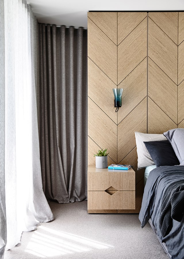 "To continue on the graphic theme showcased throughout this [striking Melbourne home](https://www.homestolove.com.au/a-striking-home-renovation-inspired-by-the-80s-5128|target=""_blank""), herringbone timber joinery has been used as feature in the master suite creating a boutique hotel vibe with a modern edge. Photo: Derek Swalwell / *Belle*"