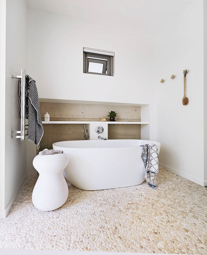 Made from river pebbles, the tactile floor tiles are a calming influence on the room. Bath and Hansgrohe tapware, from Tuck Plumbing Fixtures.