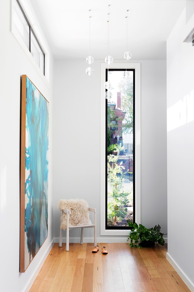Rectilinear windows frame views of greenery, balanced by a vibrant abstract painting by Tessa Dodds. *Photo:* Martina Gemmola / *bauersyndication.com.au*