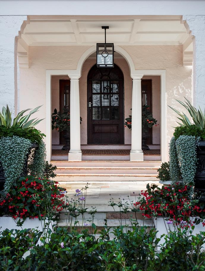 The striking combination of cascading silver falls (Dichondra argenta), furcraea, and geranium fill two oversized urns flanking the porte cochère.
