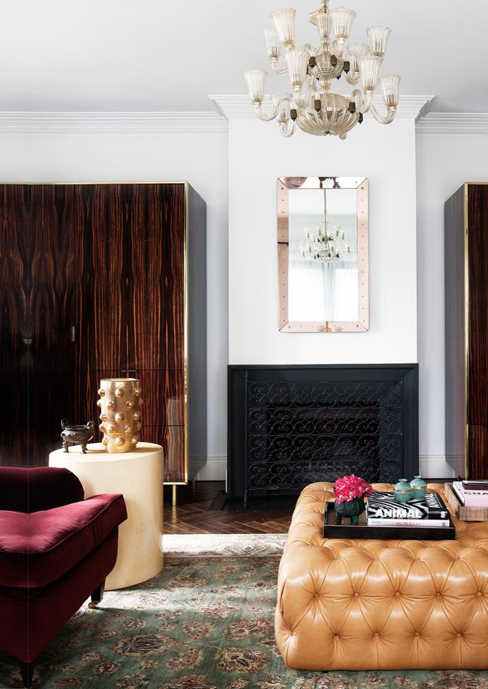 In the family room, custom armchair and leather ottoman by David Hicks. Vase on side table by Kelly Wearstler.