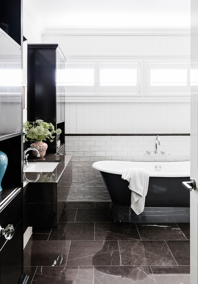 "Glossy tiles and a sleek black-and-white colour scheme has imbued this otherwise classic cottage bathroom with instant modernity. The transformation of this [timber worker's cottage](https://www.homestolove.com.au/luxurious-renovation-of-an-old-timber-workers-cottage-5159|target=""_blank"")  was slow and steady, completed over a 14-year period."