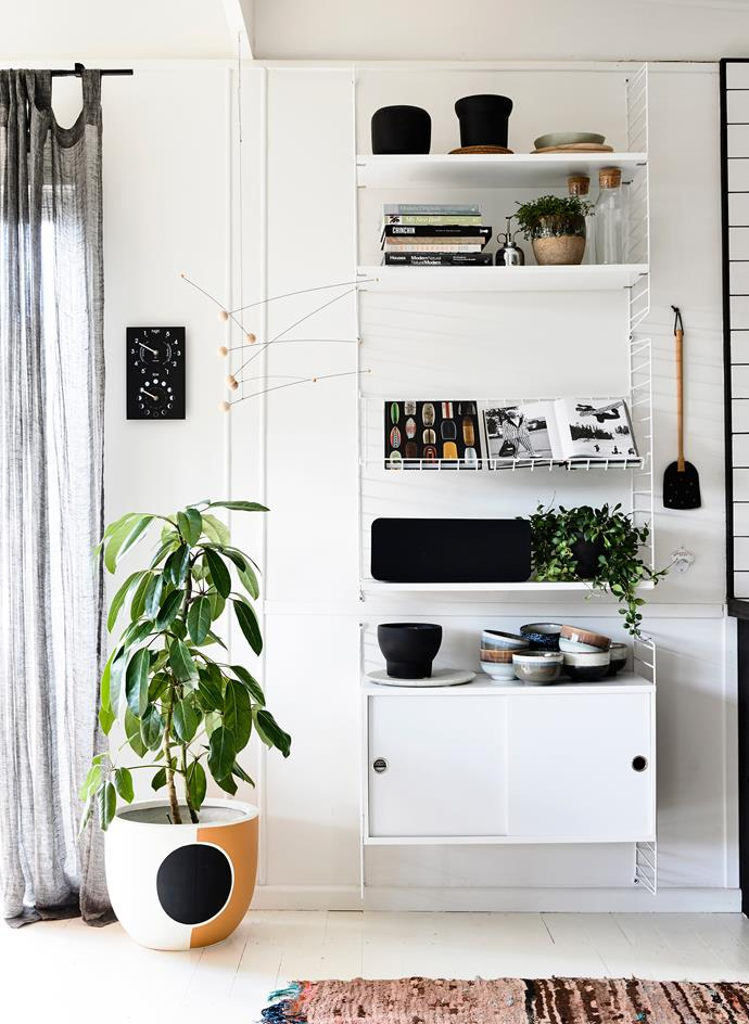 Simone has filled a wall-mounted shelving unit with books, plants and accessories.