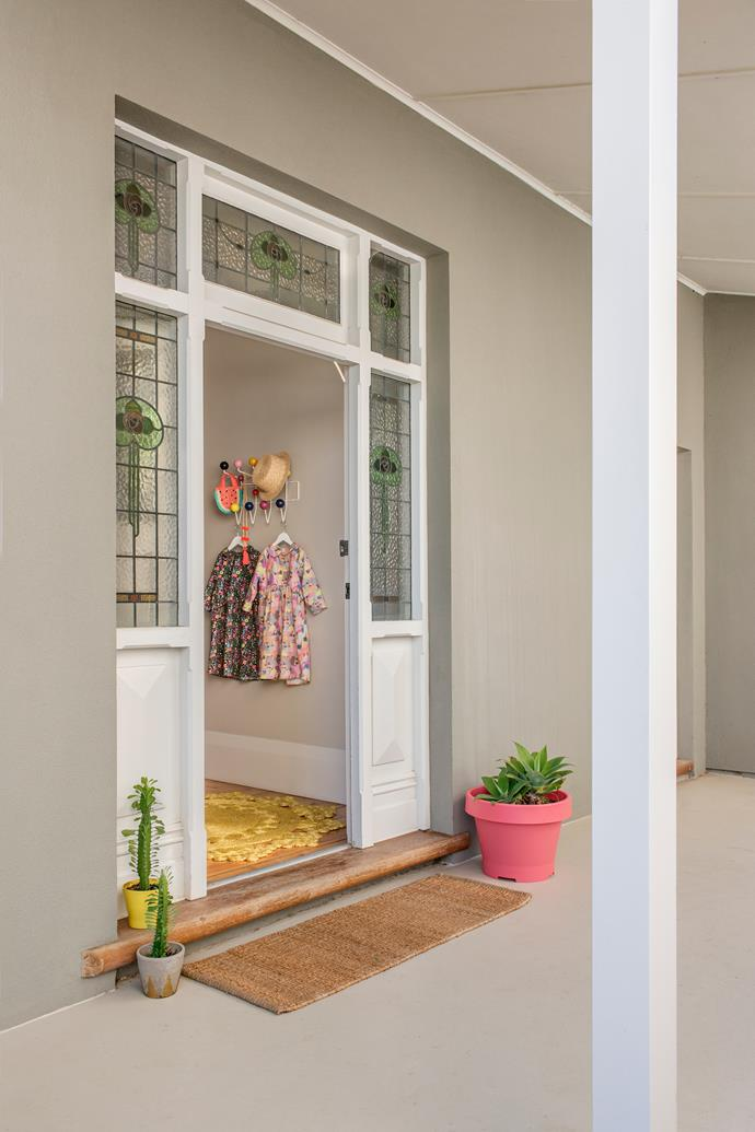 The home's exterior is painted Dulux Naval Grey. Yellow and pink pots, from Ikea and original stained glass windows create a warm welcome.