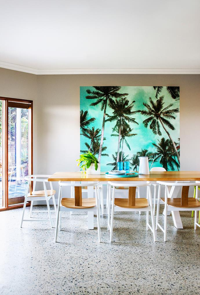 A panel of Too Palmy wallpaper from Kawaiian Lion is hung as an artwork in the dining area. Patonga dining table, from Koskela. Dining chairs, from Ikea.