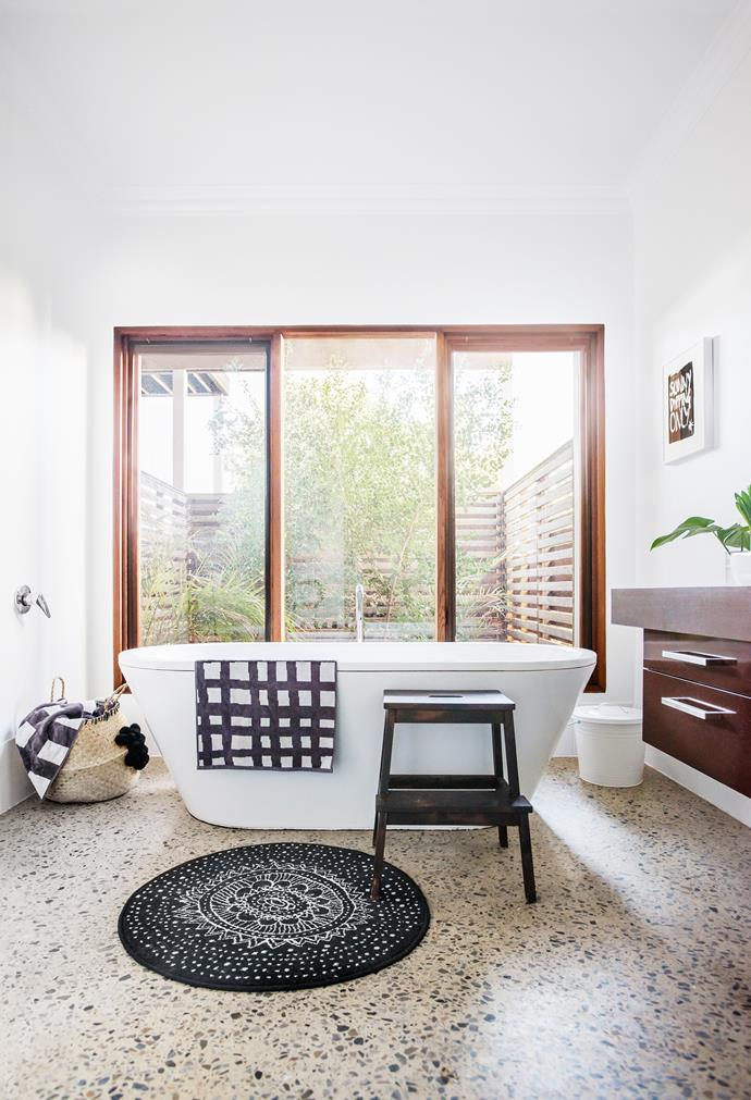 A courtyard planted with cherry guava (Psidium cattleianum) and golden cane palms creates privacy and tranquil views for bathers. Bath, from Kaldewei. Step stool and bathmat, from Ikea.