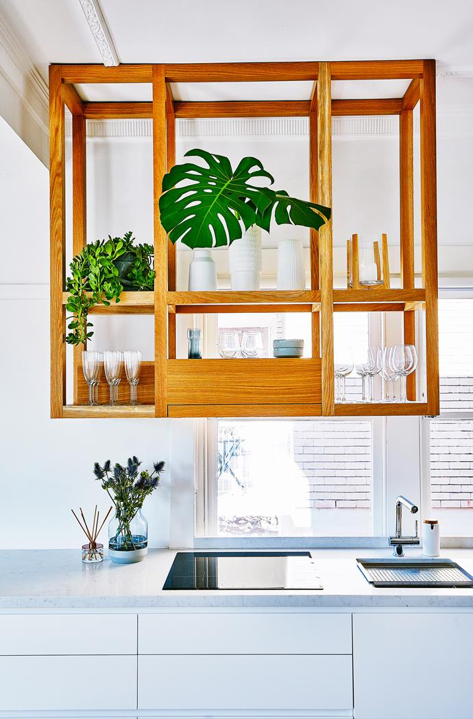 """Meg loves how the suspended timber shelving introduces a natural material into the kitchen – and that it partially blocks the view of the neighbouring building. """"It does all of this – and it looks amazing with cascading greenery,"""" she says."""