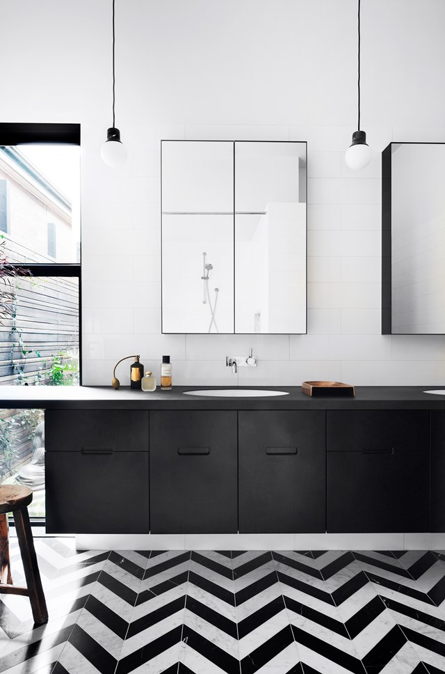 "Overlooking an east-facing courtyard, this monochromatic ensuite bathroom in a [renovated Victorian home in Melbourne](https://www.homestolove.com.au/victorian-home-changes-its-outlook-5262|target=""_blank"") feels even more spacious with the addition of generously sized mirrors and pendant lighting. Black-and-white marble tiles set in a geometric pattern add interest to the simply styled space. *Photo: Shannon McGrath / Story: Belle*"