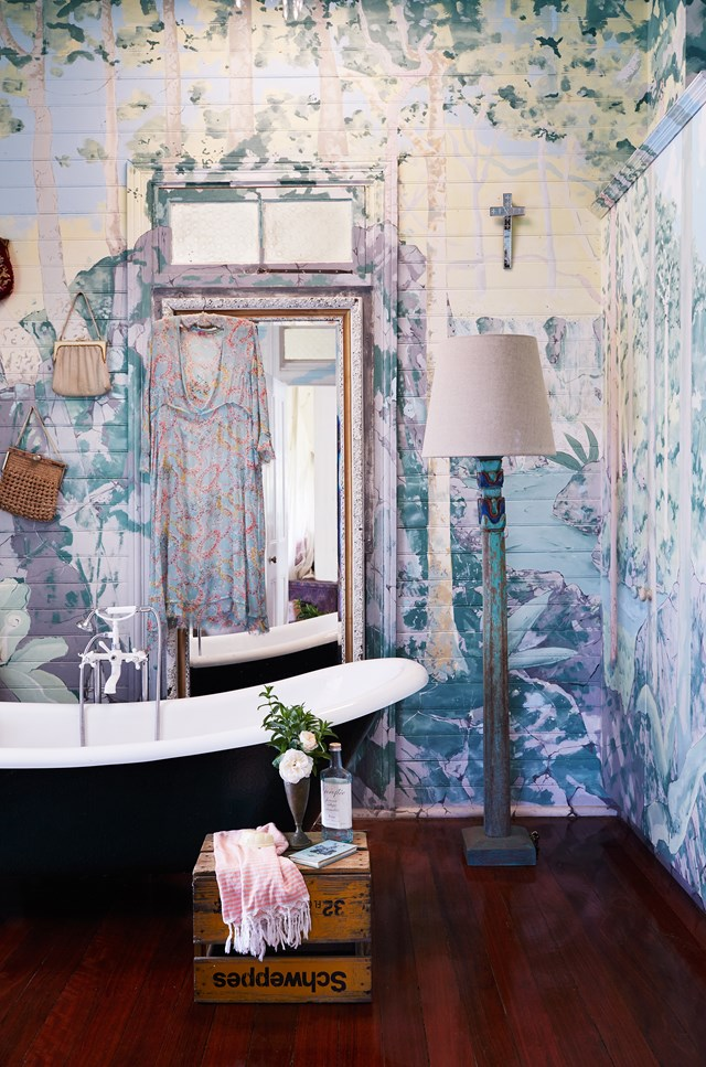"After moving into her [Byron Bay cottage](https://www.homestolove.com.au/byron-bay-federation-cottage-home-tour-5294|target=""_blank""), jewellery designer Victoria Spring decided to keep the hand-painted mural in the bathroom. An antique free-standing bathtub and timber floorboards make this an elegantly unique bathing space. *Photo: Alicia Taylor / Styling: Louise Bickle / Story: Australian House & Garden*"
