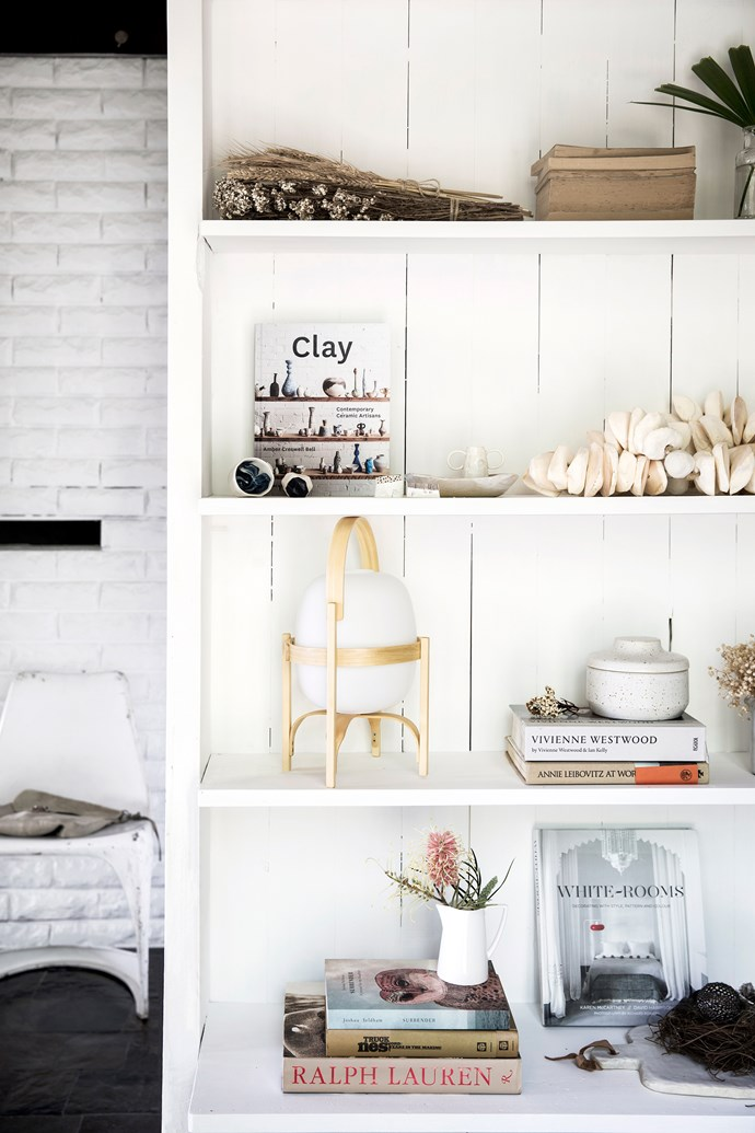 A white-painted bookshelf is a splendid backdrop for the treasures Natalie has gathered over the years. In the spirit of fresh starts, the nearby stone wall that houses the fireplace was also painted white. Ceramics by Milly Dent, Keiko Matsui, Alison Fraser and Tara Burke. Cestita lamp, Santa & Cole. The Jasper Conran for Wedgwood jug was a wedding present. Chair, Garden Life.