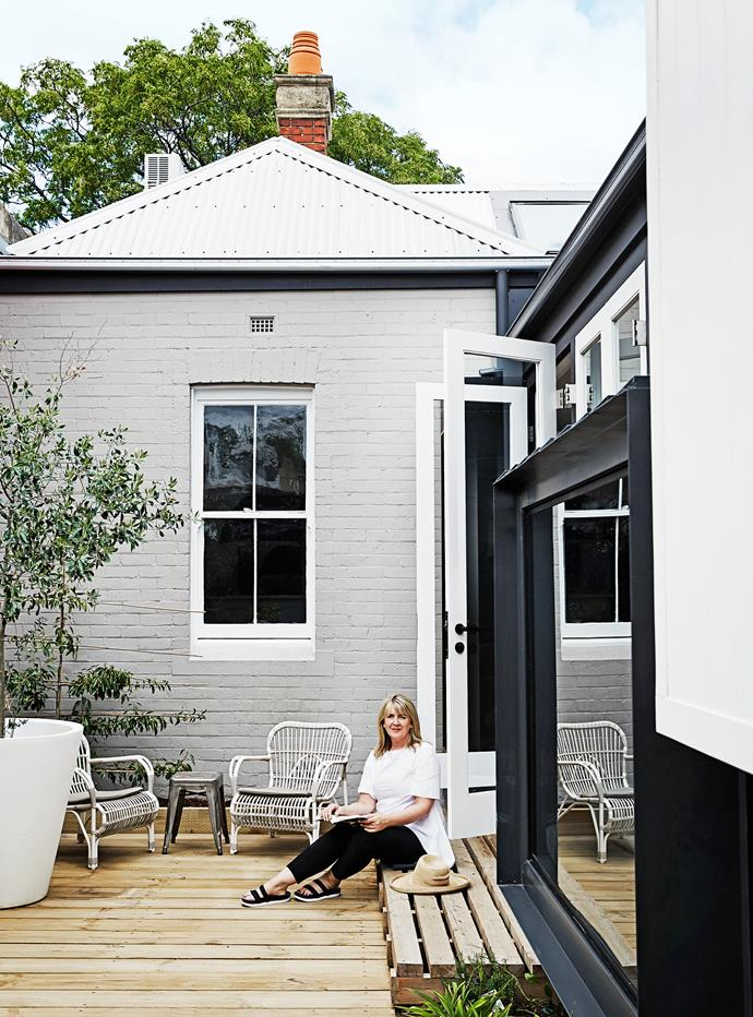 """Carole sits on treated pine sleepers, deliberately left raw. The red brick wall was painted in Dulux """"Ghosting"""". """"I wanted softer tones for the house to keep it a calm environment,"""" Carole explains."""