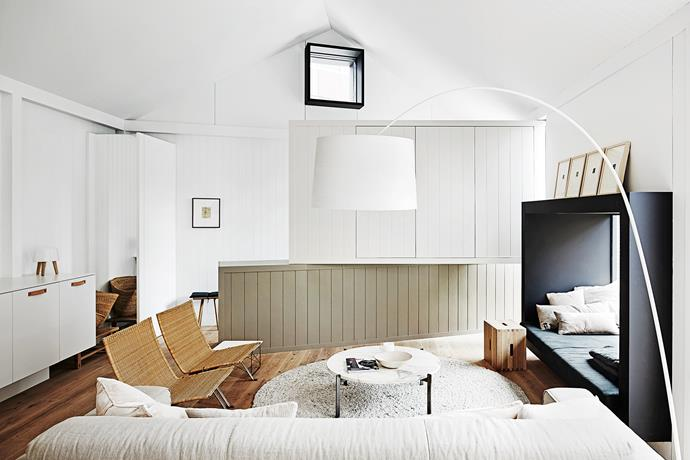 """Two joinery boxes were slid into the living room space to square it off and conceal a utility room and hide the TV. The lower wall is the same colour as the kitchen cupboard – Dulux """"Mud Pack"""" – but double strength."""