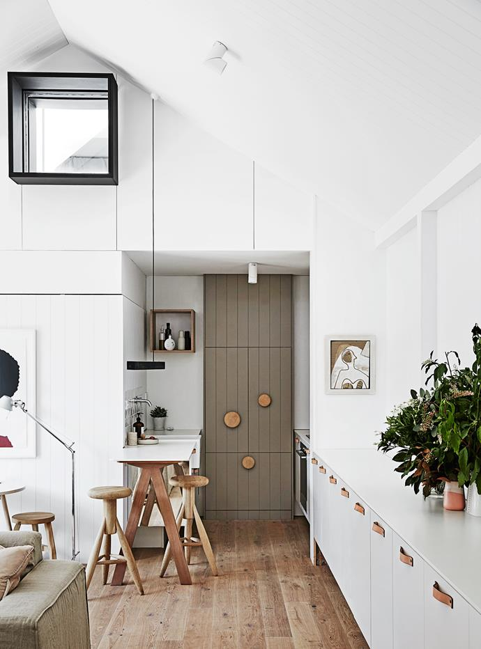 """The working end of the kitchen was created in what was part of the original bathroom. A fridge hides behind cupboard doors painted in Dulux """"Mud Pack""""."""