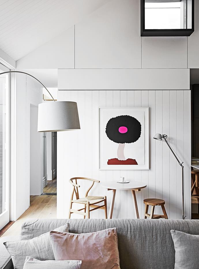 """""""This is my drinking-tea-while-I-check-my-emails space,"""" Carole says. David Band artwork Happiness hangs above a Hans Wegner """"Wishbone"""" chair."""