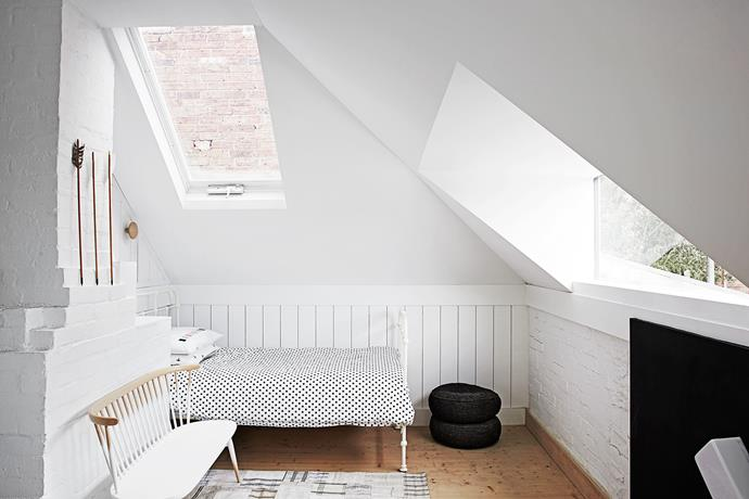 The addition of skylights and white walls create a light and bright bedroom. The stair wall (just seen) is painted in chalkboard paint.