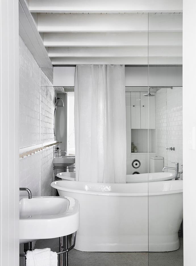 The ensuite bathroom is small, but the mirror makes it appear larger, and there's still room for a bath. Storage includes full-height shelving that looks like part of the panelled door next to the basin.