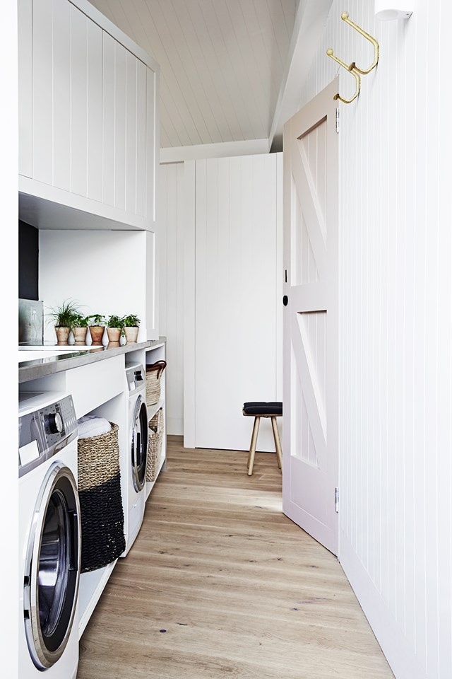 "This loveable laundry doubles as a butler's pantry (talk about a hardworking space!). White timber panelling, a blush pink door and hints of gold up the style stakes, tying in perfectly with the rest of Scandinavian decor and design features in this [restored Edwardian home](https://www.homestolove.com.au/creative-restoration-of-an-old-edwardian-house-5316|target=""_blank""). Photo: Sharyn Cairns / *real living*"