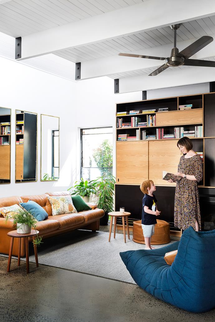 In the living room, warm timbers, tan leather and a cosy rug make a snug counterpoint to cool concrete. Entertainment unit, from Woodbeast. Togo chair, from Ligne Roset. Ottoman, from Hunting for George.