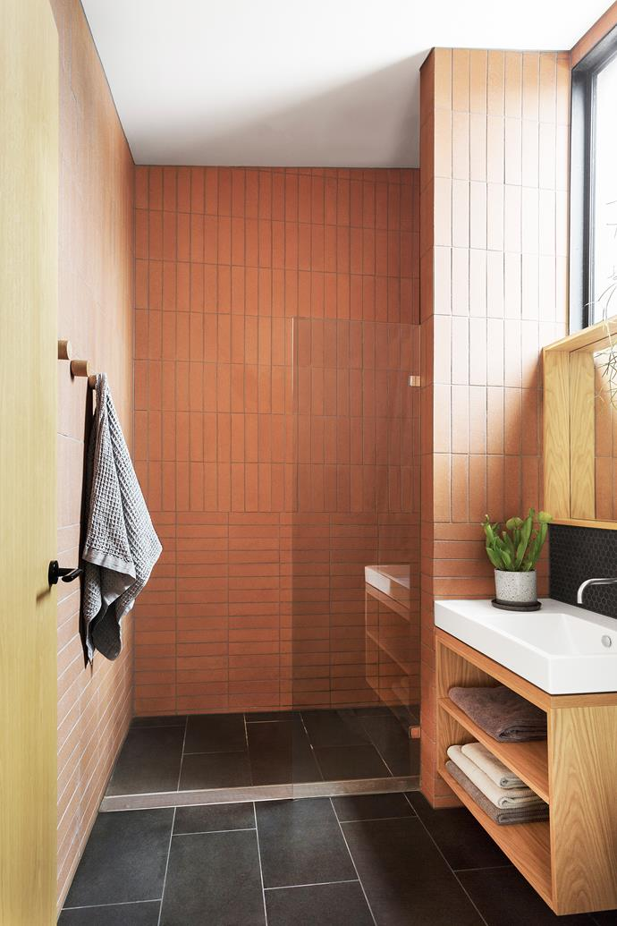 """Having our own bathroom is just brilliant,"" says Alice. Terracotta wall tiles, from Artedomus. Mosaic splashback tiles and honed basalt floor tiles, from Classic Ceramics. Custom vanity in American oak veneer."