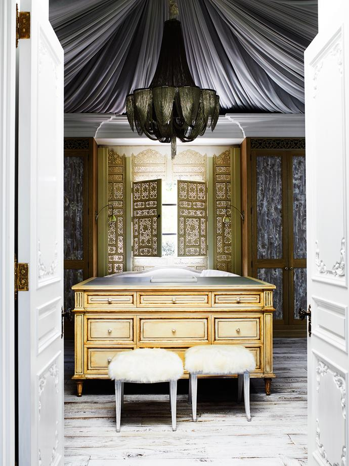 The wardrobe has a chandelier by Juliettes Interiors London. Repurposed window screen from Galleria d'Epoca Florida. Swedish neoclassical stools. Dressing room island custom made by Adam Hart.