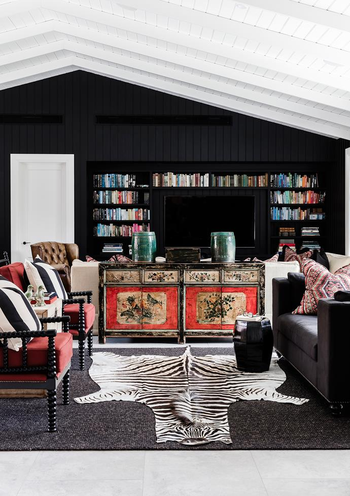 Books and accessories in the games room are highlighted by the wall in Dulux Black.