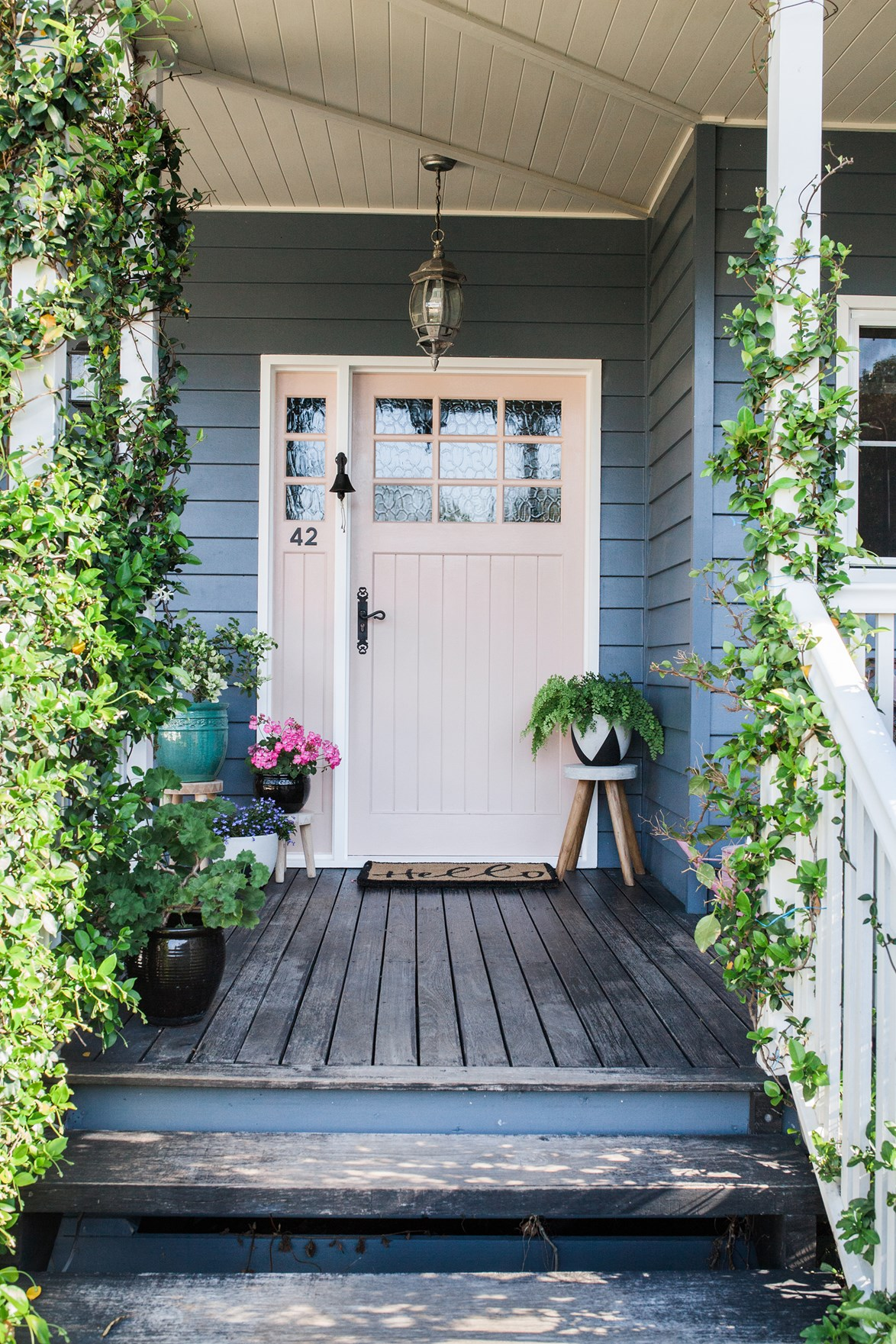How gorgeous is the pale pink door against the grey exterior? It wins our prettiest door prize! A Moroccan style pendant, potted plants and climbing vines just add to the charm.