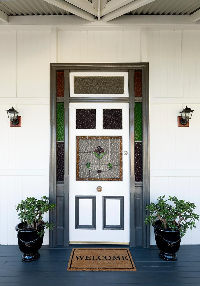 A stunning period door with cute paint-framed panels. The plants and mat complete the look.