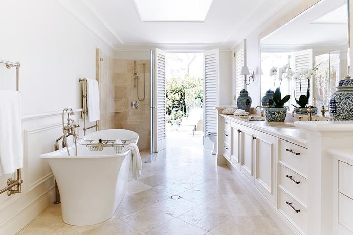 French doors open to a tranquil garden view. The vanity counter and flooring are in Saturnia travertine from Artedomus.