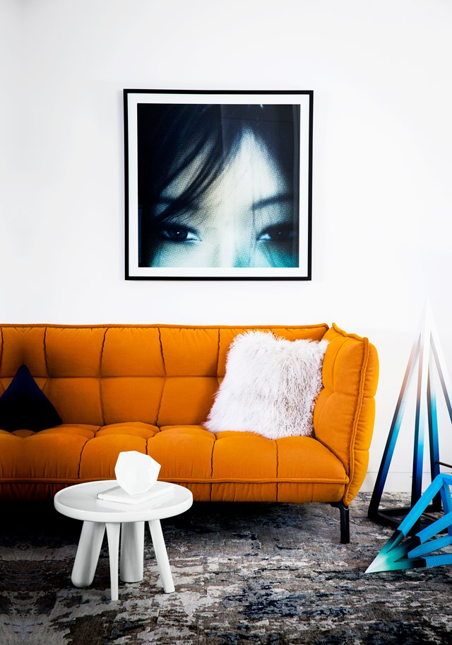 """A statement orange couch by B&B Italia is paired with complementary blue toned artworks. The end result is an unexpectedly punchy minimalist living space hidden behind the classic exterior facade of this [stately Melbourne home](https://www.homestolove.com.au/stately-melbourne-home-fit-out-by-interior-designer-adele-bates-5427
