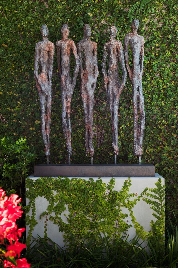 A sculpture by Ann Vrielinck sits in front of wall covered in *Ficus pumila*.