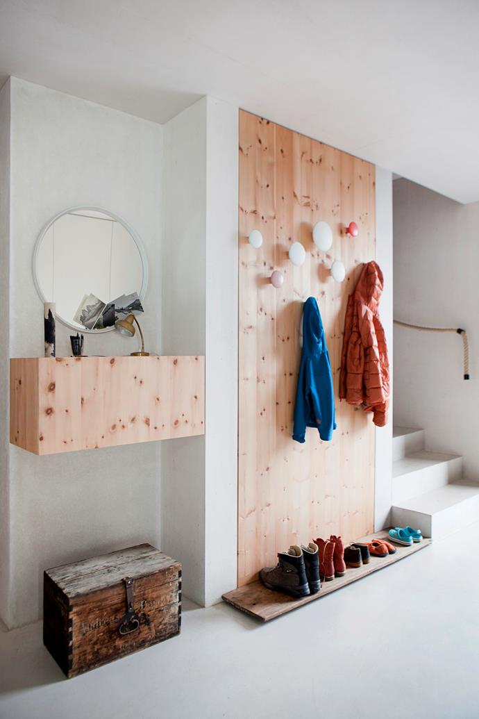 Coats hang from Muuto wall hooks in the entrance on the middle floor. The stairs lead to the upper floor. The bedrooms and bathrooms are all on the lower floor, while the kitchen and living spaces are on the middle floor.